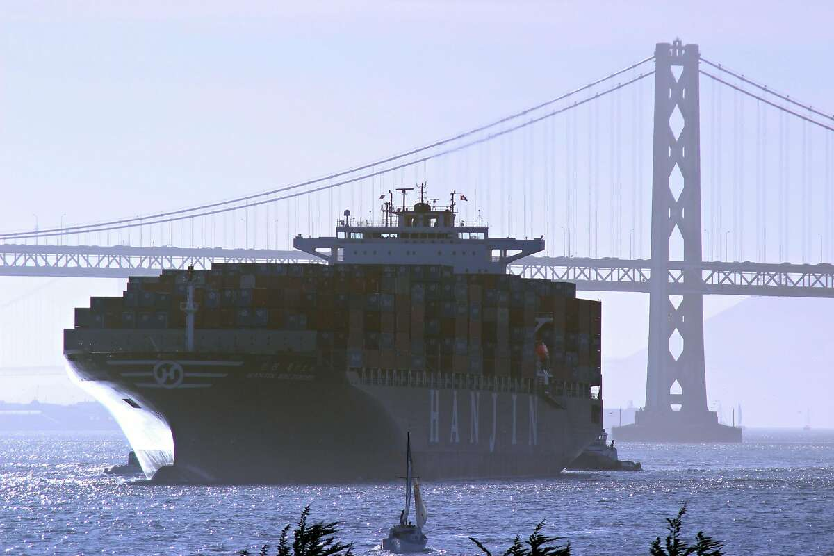 A cargo ship passes by the Bay Bridge in Oakland, California.