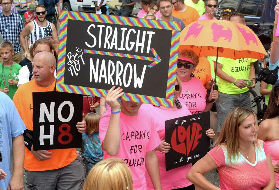 Supporters hold signs while walking along Orleans Street during Beaumont's first Pride Parade on Saturday.   Photo taken Saturday, June 21, 2014  Guiseppe Barranco/@spotnewsshooter Photo: Guiseppe Barranco, Photo Editor