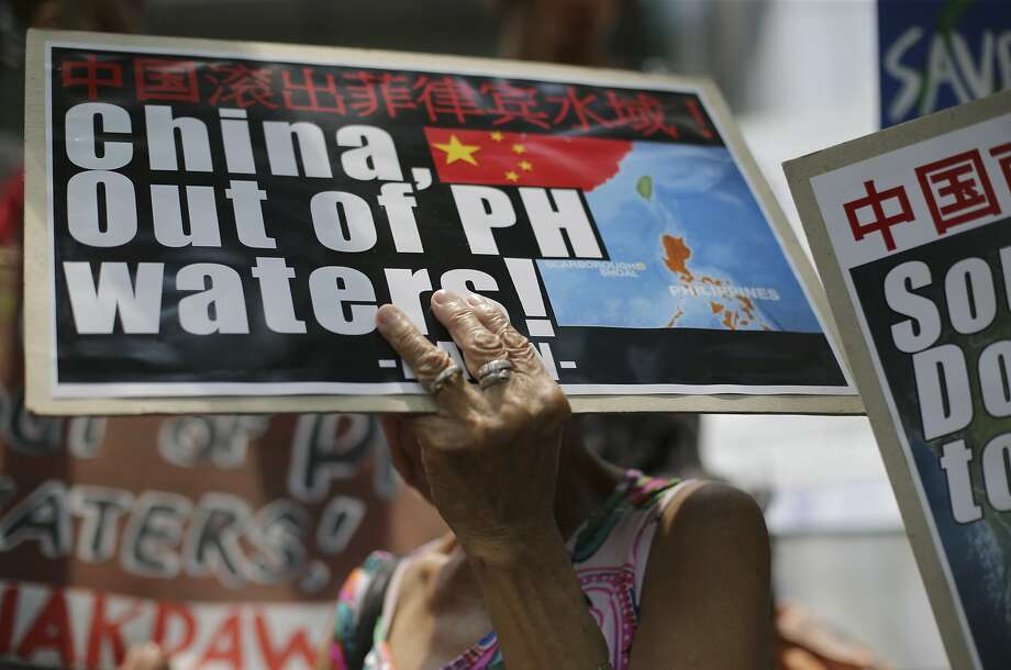 A Filipino uses an anti-China sign to shade her head as she joins a rally outside a Chinese Consulate to protest actions in the disputed South China Sea. Photo: Aaron Favila, Associated Press