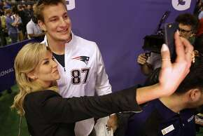 """FILE - In this Jan. 27, 2015, file photo, New England Patriots' Rob Gronkowski poses for a selfie with television host and sportscaster Charissa Thompson during media day for NFL Super Bowl XLIX football game in Phoenix. Men are behind more news stories than women by a nearly 2-to-1 margin across print and television platforms, though there was a slight increase in bylines and credits for women last year, a new study says. The Washington-based Women's Media Center released its study Thursday, June 4, 2015,  as part of its fourth annual report on """"The Status of Women in U.S. Media.""""(AP Photo/David J. Phillip, File)"""