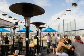 Patrons enjoy drinks with a view of the city skyline on the roof at El Techo in San Francisco Calif., Sunday, September 28, 2014