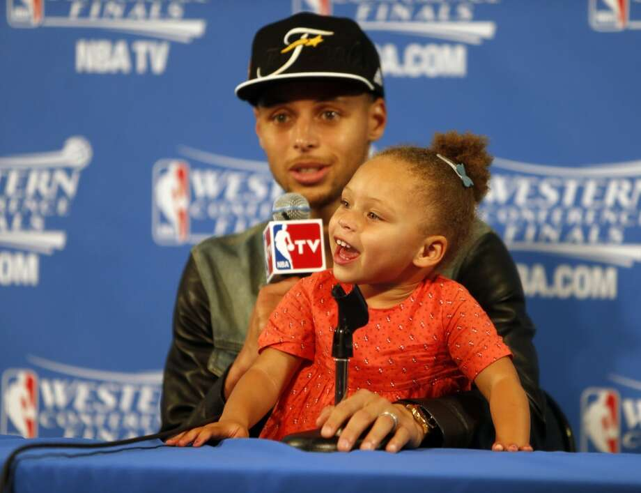 Golden State Warriors' Stephen Curry speaks to the media as his daughter Riley plays after Warriors' 104-90 win over Houston Rockets in Game 5 of NBA Playoffs' Western Conference Finals at Oracle Arena in Oakland, Calif., on Wednesday, May 27, 2015. Photo: Scott Strazzante, The Chronicle