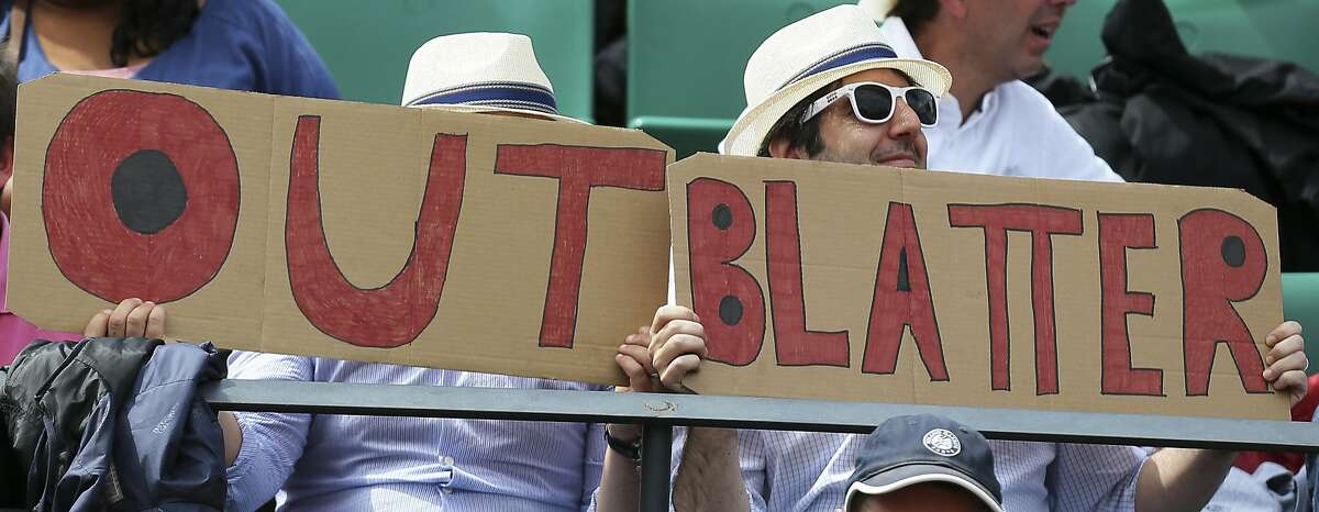 """Two spectators hold signs reading """"Out Blatter"""", referring to newly re-elected FIFA president Sepp Blatter during the quarterfinal match of the French Open tennis tournament between Spain's Garbine Muguruza and Lucie Safarova of the Czech Republic at the Roland Garros stadium, in Paris, France, Tuesday, June 2, 2015."""