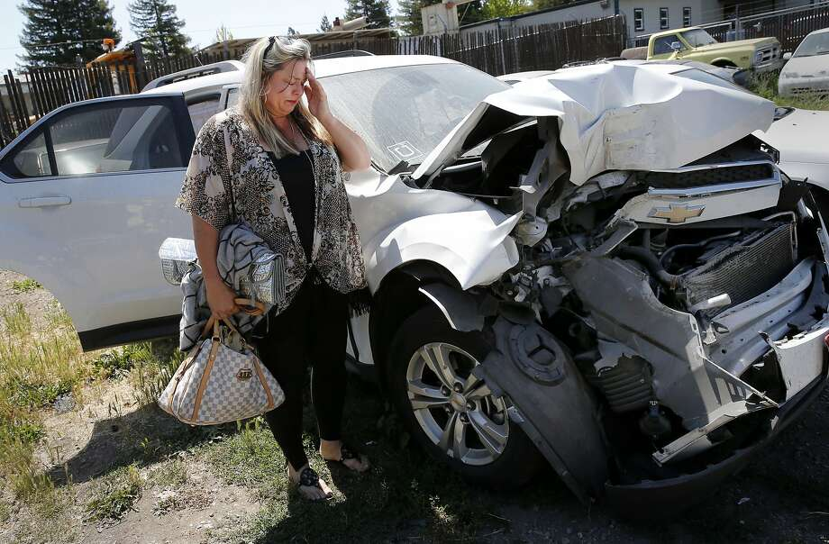 Traci Beitz stands next to her Chevy Equinox after retrieving a few personal items Thursday June 4, 2015. Traci Beitz got in an accident while she had her Uber application on and was awaiting ride requests in Napa, Calif.  Her car was totaled and Uber now says she was not insured at the time. Photo: Brant Ward, The Chronicle