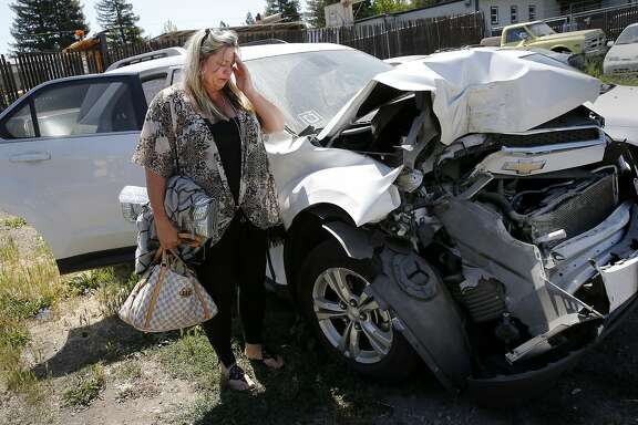 Traci Beitz stands next to her Chevy Equinox after retrieving a few personal items Thursday June 4, 2015. Traci Beitz got in an accident while she had her Uber application on and was awaiting ride requests in Napa, Calif.  Her car was totaled and Uber now says she was not insured at the time.