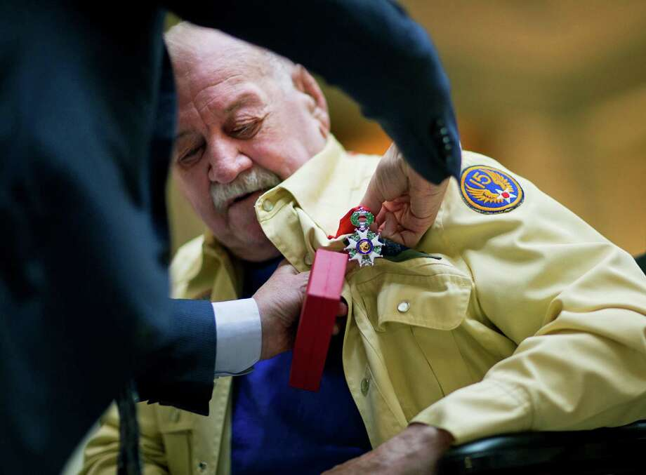 World War II veteran Julian Fleming, 92, of Cumming, Ga., is pinned with the French Legion of Honor by Denis Barbet, the consul general of France in Atlanta, during a ceremony at the Capitol Thursday, June 4, 2015, in Atlanta. The Legion of Honor is the highest distinction France can award to a citizen or foreigner. The Ten WWII veterans from Georgia who were honored Thursday fought on French territory as part of the liberation of the country from Nazi Germany and were nominated by President Francois Hollande. Fleming flew 52 combat bombing missions and received the Purple Heart for injuries incurred during an explosion from German anti-aircraft.  Photo: David Goldman, Associated Press / AP