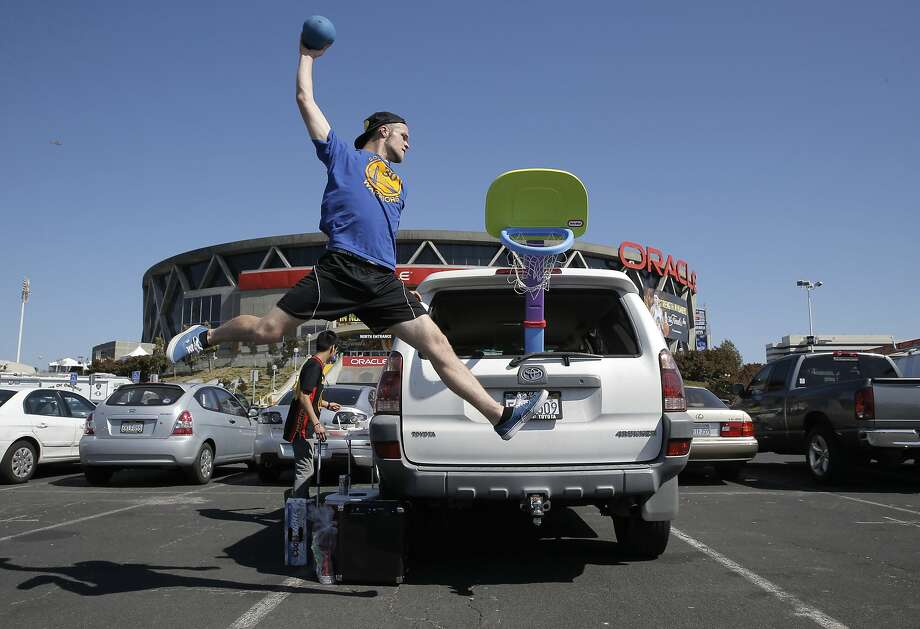 John Breslow of Castro Valley goes up for a shot while waiting in the parking lot for the doors to open, as the Golden State Warriors prepare take on the Cleveland Cavaliers in Game one of the NBA finals at Oracle Arena, in Oakland, Calif., on Thurs. June 4, 2015. Photo: Michael Macor, The Chronicle