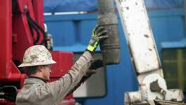 A rig hand removes drill pipe from a natural gas well owned by EQT Corp. at a hydraulic fracturing site located atop the Marcellus Shale. Shale producers have been pumping out more oil and gas than the EIA has estimated. For example, the agency last month expected the Marcellus to pump out 15.2 billion cubic feet of natural gas this month. That was revised to 15.9 billion this week.