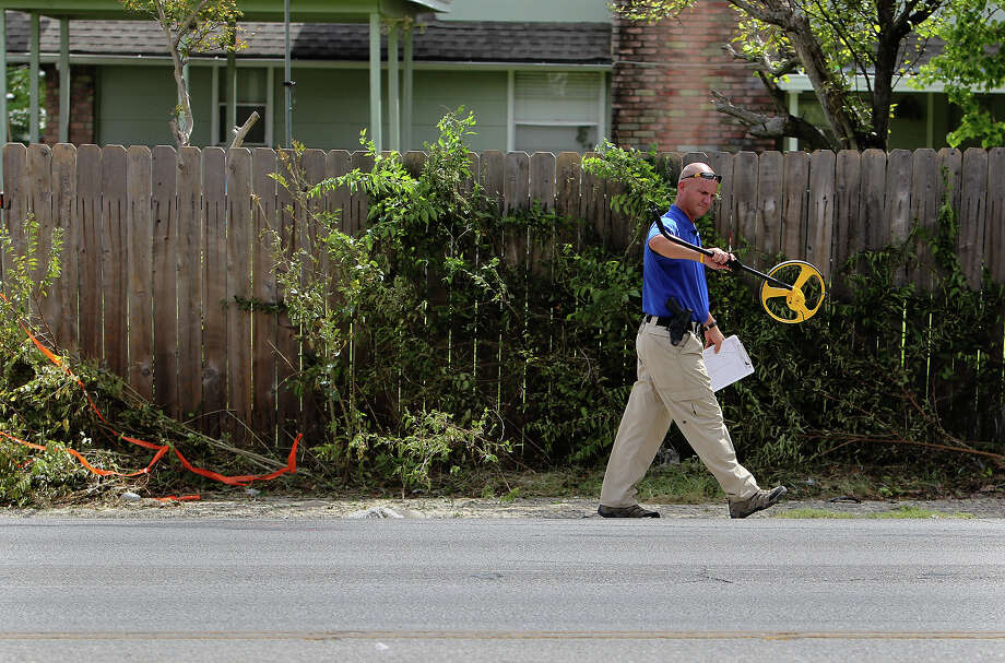An investigator works at the scene of an accident in which bicylist Devan Coulter Smith was killed in September 2012 on West Avenue north of Silver Sands Drive. Photo: San Antonio Express-News File Photo / San Antonio Express-News
