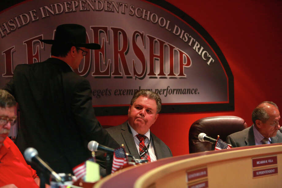 Southside Independent School District trustee Loren Brewer shakes the hand of Superintendent Ricardo Vela (seated) after the board voted to place Vela on indefinite leave. Photo: Lisa Krantz /San Antonio Express-News / ©2015 San Antonio Express-News