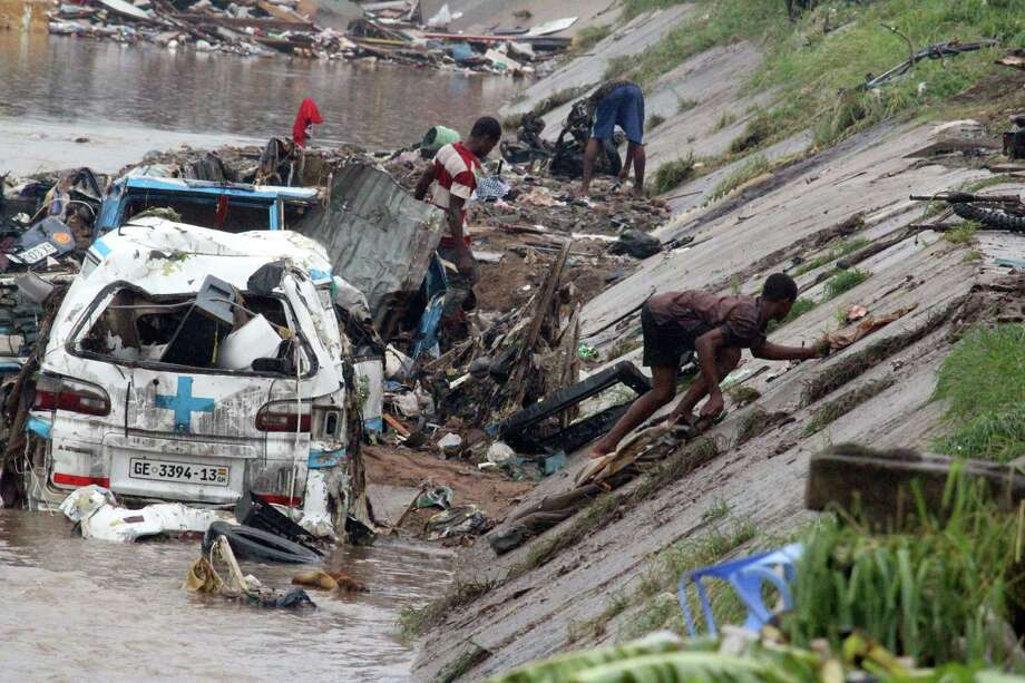 Rescuers try to remove valuables submerged in a flood after at least 90 people were killed in a petrol station fire in Ghana's capital, Accra, on June 4, 2015. The death toll from a huge gas station explosion and flooding in Ghana's capital has more than doubled to 150 people, the president said Thursday night. Dozens of people had sought shelter at the gas station and in nearby shops in central Accra to escape the torrential rains at the time of Wednesday night's blast. Flooding swept fuel being stored at the station into a nearby fire, triggering the explosion that also set ablaze neighboring buildings, officials said.  AFP PHOTO / FATI BRAIMAH FATI BRAIMAH/AFP/Getty Images Photo: FATI BRAIMAH /AFP / Getty Images / AFP