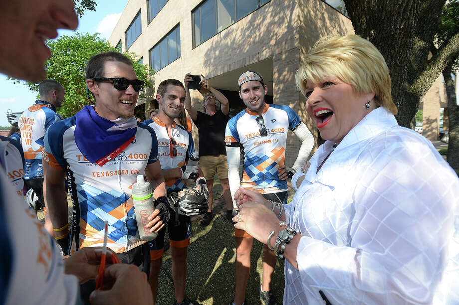 Members of the Texas 4,000 team, including local Layla Nejad, are greeted by Mayor Becky Ames after arriving at City Hall Thursday. The team is part of a more than 4,000 mile trek across the country to help raise funds for cancer research. Seventy-two riders are taking part in the event this year, with some riding in memory of loved ones lost to cancer. The ride started in 2004 among students at the University of Texas at Austin. Each year since, 72 riders, chosen from hundreds who apply to join, make the journey from Austin to Anchorage, Alaska. Beaumont native Nejad, who is riding with the Ozarks team, helped add an additional route to the trip, taking her team through southeast Texas and into Louisiana, which have high rates of cancer. The group of 27 riders spent the night at Lamar University, but first made a stop to the Spindletop Museum, where the replica gusher, designed and built by Nejad's father Sina Nejad, was turned on as a special treat for the team.