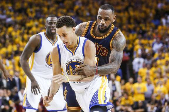 Golden State Warriors' Stephen Curry is guarded by Cleveland Cavaliers' LeBron James in the second period during Game 1 of The NBA Finals on Thursday, June 4, 2015 in Oakland, Calif.