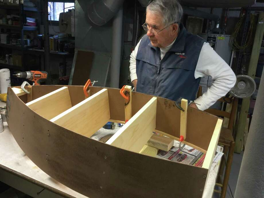 "Jack Button works on the boat-shaped book box that will be used as a ""Little Library'' in Milford. Photo: Contributed Photo /Friends Of The Milford Library"