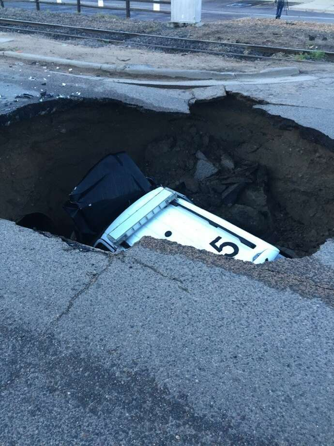 A police SUV was swallowed by a 15-feet deep sinkhole Friday morning near Denver following torrential storms that hit the area. Photo: Mark Campbell/Sheridan Police Department