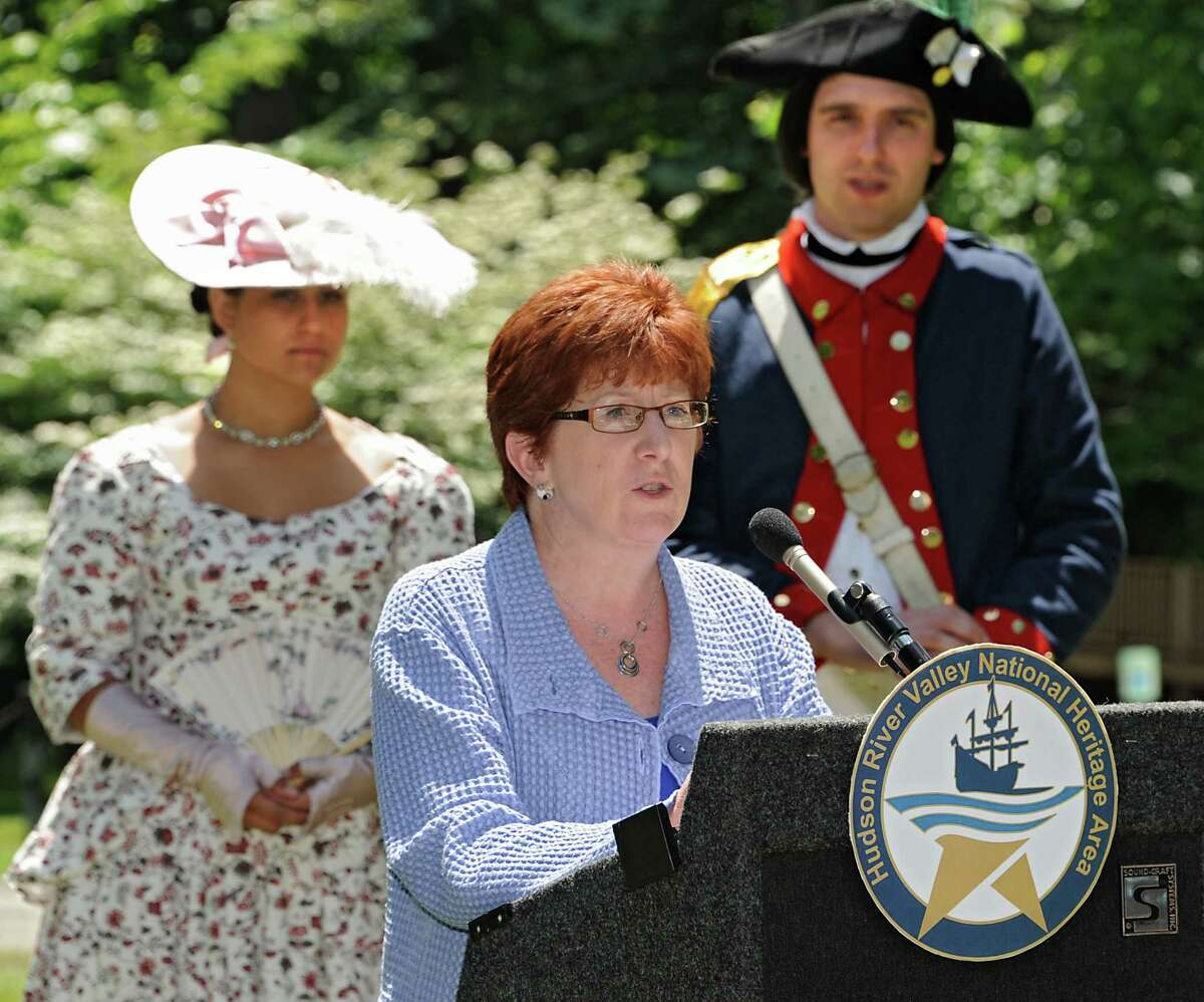 Albany Mayor Kathy Sheehan speaks during a press conference announcing seven National Heritage Area Heritage Development Grants to historical and cultural institutions in the upper Hudson Valley at the Ten Broeck Mansion gardens on Friday, June 5, 2015 in Albany, N.Y. Standing in the background are living history reenactors Lisa Nunez and Chad Johnson of New Windsor Cantonment State Historic Site. (Lori Van Buren / Times Union)