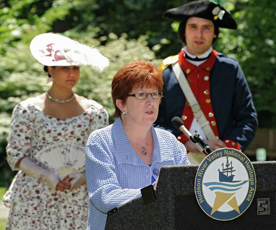 Albany Mayor Kathy Sheehan speaks during a press conference announcing seven National Heritage Area Heritage Development Grants to historical and cultural institutions in the upper Hudson Valley at the Ten Broeck Mansion gardens on Friday, June 5, 2015 in Albany, N.Y. Standing in the background are living history reenactors Lisa Nunez and Chad Johnson of New Windsor Cantonment State Historic Site. (Lori Van Buren / Times Union) Photo: Lori Van Buren / 00032164A