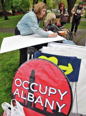 """Occupy Albany protester Megan Hansen of Albany writes out a schedule for a """"teach-in"""" as demonstrators begin to assemble in Lafayette Park in Albany Tuesday afternoon May 1, 2012.    (John Carl D'Annibale / Times Union archive) Photo: John Carl D'Annibale / 00017486A"""