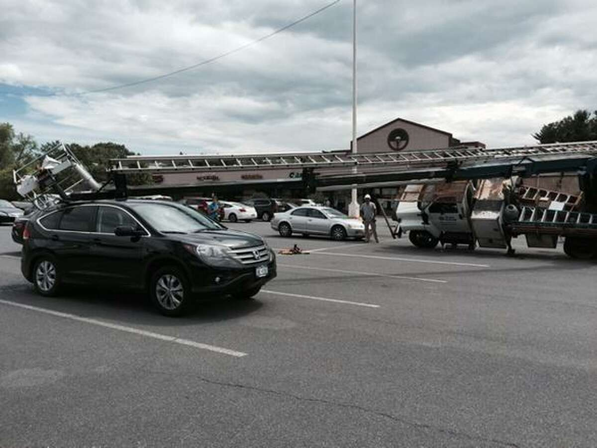 A boom truck in Hamilton Square, Guilderland, changing lights in a parking lot tipped, crushing a Honda SUV on Friday, June 5, 2015. (Paul Grondahl/Times Union)