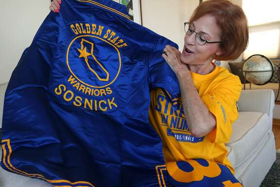 Longtime Warriors fan Leslie Sosnick unfolds a complete team uniform, presented to her father Peter Sosnick during the team's 1974-1975 championship season on his 48th birthday, at her home in Oakland, Calif. on Friday, June 5, 2015. Sosnick attended her first Warriors game when the team played at the San Francisco Civic Auditorium on her ninth birthday in 1963 and has been hooked ever since. She is currently number two on the Warrior's season ticket holder priority list.