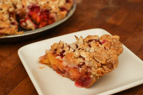 A slice of peach raspberry pie with almond streusel topping is seen in Amy Machnak's San Francisco home Friday, June 5, 2015.