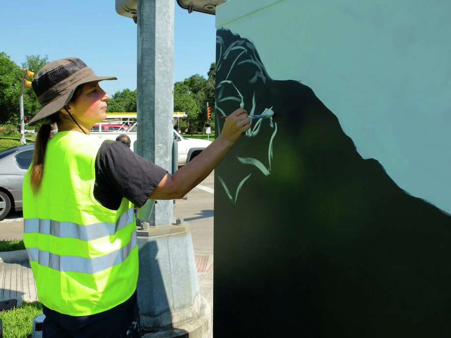 "Artist Anat Ronen began painting the 8x4-foot traffic signal control cabinet at the corner of West Bellfort and Willowbend Streets with a morning glory design Thursday morning. By the day's end she had finished the first of 31 planned ""mini murals"" by street artists in a new program organized by UP Art Studio and supported by various municipal programs and organizations. Photo: Molly Glentzer"