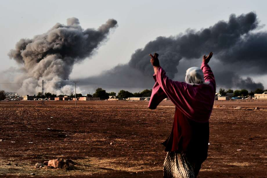 A woman reacts as smoke rises from the the Syrian town of Ain al-Arab, known as Kobane by the Kurds, after a strike from the US-led coalition. Photo: Aris Messinis, AFP/Getty Images