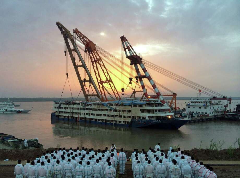 Paramilitary policemen wait to recover bodies Friday from the Eastern Star after the vessel was righted and lifted by cranes in the Yangtze River in China. Officials say its unlikely there are more survivors. Some 339 people are missing. Photo: STR / CHINATOPIX