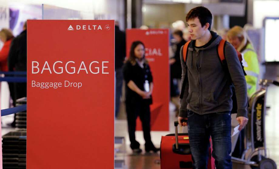 Travelers walk toward the baggage drop area for Delta Air Lines at the Seattle airport. Delta is preloading carry-ons on some flights this summer. Photo: Elaine Thompson, STF / AP