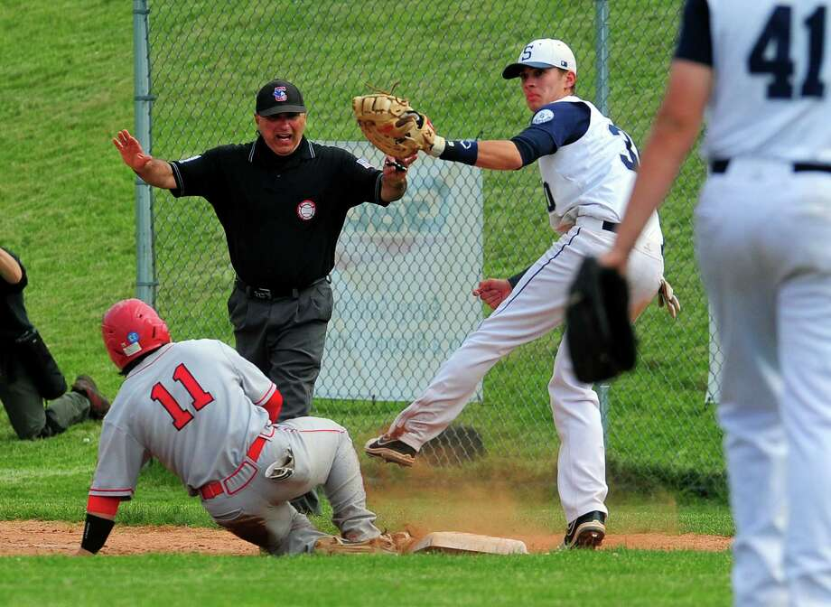 Greenwich's Marco Pastore slides back to first as Staple's Ross Poulley attempts to pick him off, during Class LL baseball quarterfinals action in Westport, Conn., on Friday June 5, 2015. Photo: Christian Abraham, Staff Photographer / Connecticut Post