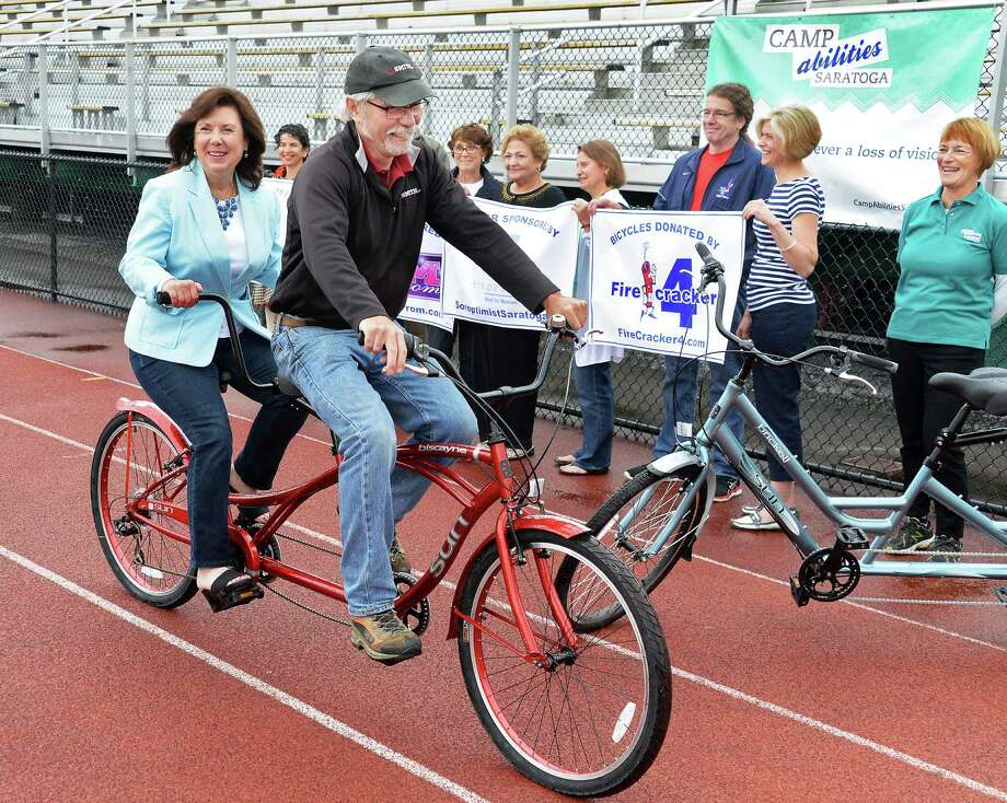 "Gale Veitch, left, of Saratoga Mom Prom and Peter Gontos, race director for Firecracker 4, ride a tandem bikes during a news conference for the Saratoga Springs Lions ""Camp Abilities Saratoga"" at Skidmore College Friday June 5, 2015 in Saratoga Springs, NY.  (John Carl D'Annibale / Times Union) Photo: John Carl D'Annibale / 00032100A"