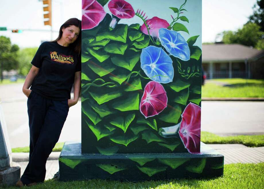 Street artist Anat Ronen on Thursday painted morning glory vines on a traffic control cabinet.  Photo: Marie D. De Jesus, Staff / © 2015 Houston Chronicle
