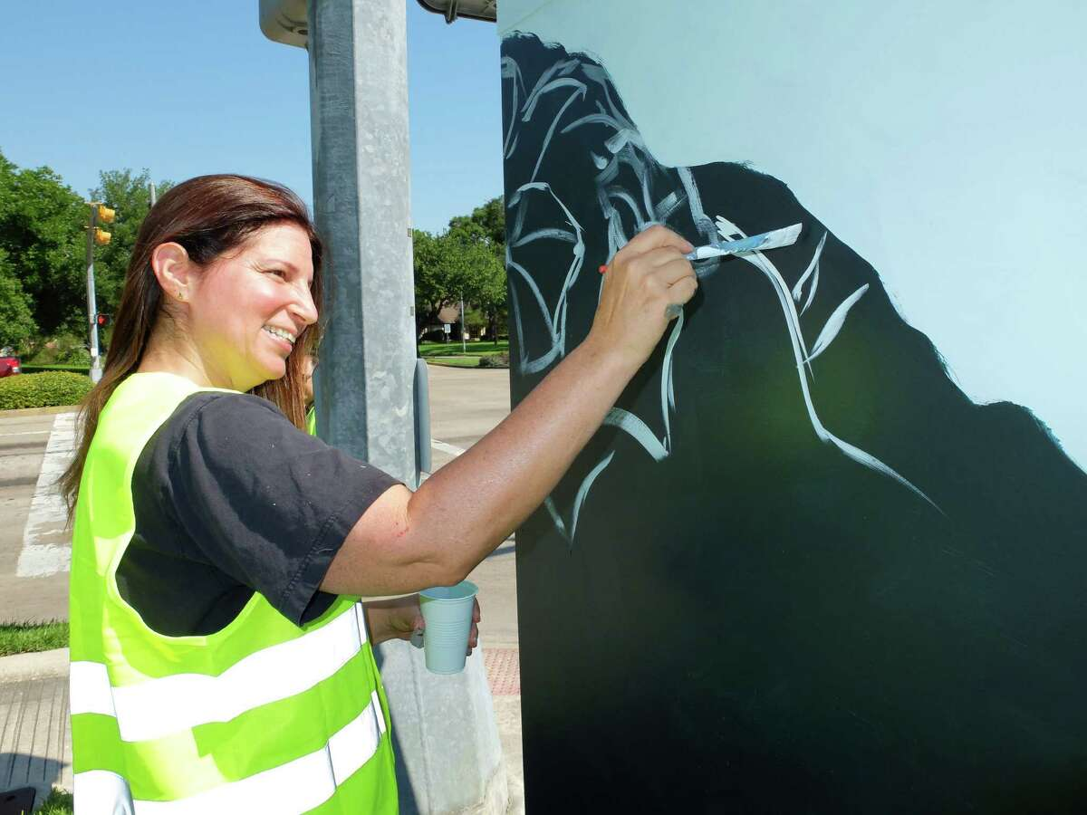 """Artist Anat Ronen began painting the 8x4-foot traffic signal control cabinet at the corner of West Bellfort and Willowbend Streets with a morning glory design Thursday morning. By the day's end she had finished the first of 31 planned """"mini murals"""" by street artists in a new program organized by UP Art Studio and supported by various municipal programs and organizations."""