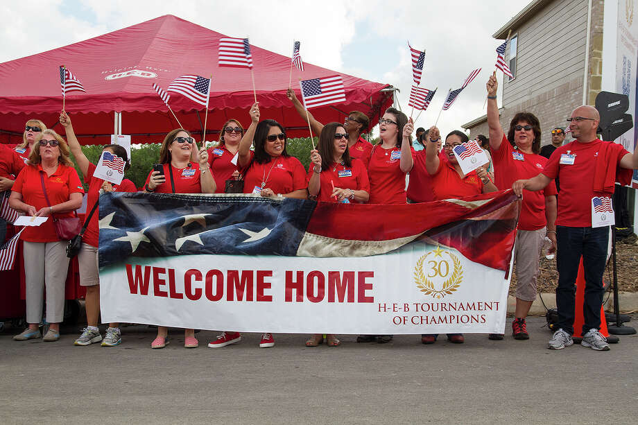 HEB partners line up to welcome the Range and Robinson families who are gifted a new mortgage-free, fully funished home as part of the H-E-B Tournament of Champions program partnered with Operation Finally Home and PulteGroup,  Friday, June 5, 2015 in the Champions Park neighborhood. The military families were chosen by Operation Finally Home, a national nonprofit organization dedicated to building homes for wounded, ill or injured veteran and their families. Photo: Alma E. Hernandez, For The San Antonio Express News / Alma E. Hernandez / For The San