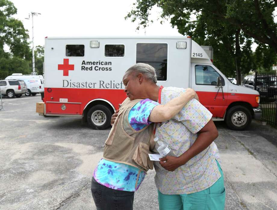 Marla Pirtle gets a hug Friday from Red Cross volunteer Susan Scott at a mobile registration intake center in Meyerland. Pirtle and her husband came for assistance with food and clothing.  Photo: Jon Shapley, Staff / © 2015 Houston Chronicle