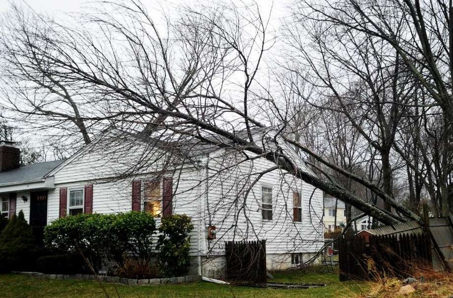 A tree lies on a home at 5 Northridge Road in Old Greenwich Saturday afternoon, March 13, 2010. High winds and rain left roads covered in brush and downed wires causing traffic tie ups on both the Merritt Parkway and I-95. Photo: Keelin Daly / Greenwich Time