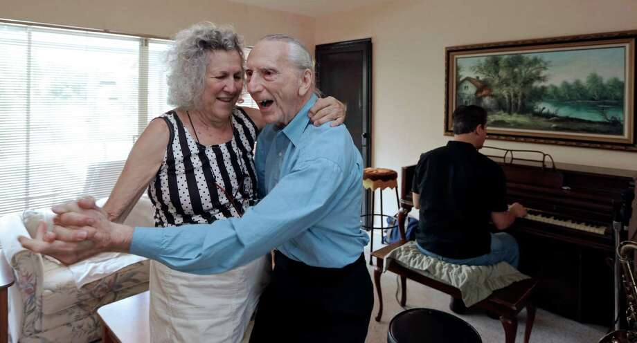 Saundra and Al Karp dance as son Larry plays piano at their home in North Miami Beach, Fla. The trio performs old standards locally to ease stress and help raise money to save the home from foreclosure.  Photo: Alan Diaz, STF / AP