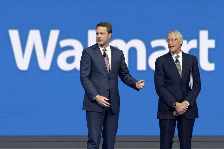 International employees cheer at the Wal-Mart shareholder meeting in Fayetteville, Ark. The company said that board Chairman Rob Walton, a son of Wal-Mart founder Sam Walton, will step down and be succeeded by Vice Chairman Greg Penner, who is his son-in-law. Photo: Danny Johnston, STF / AP