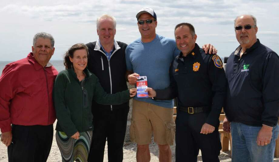 Police Captain Sam Arciola, Police Athletic League president,, second from right,  is shown holding ticket number one for the annual Fireworks Celebration that will take place June 3 at Compo Beach. Also in the photo are, from left to right, Bill Chappa of PAL; Melissa Bernstein, fireworks sponsor: Harold Friedman of PAL; Doug Bernstein, fireworks sponsor; Arciola and Dan DeVito of the town's Parks and Recreation Department. Photo: Contributed Photo / Contributed Photo / westport news