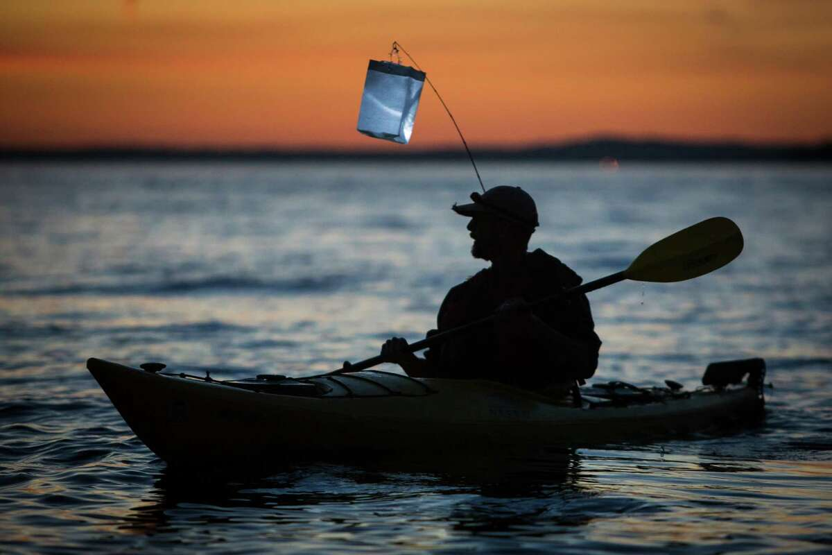 A kayaktivist paddles with a lantern during the Shell No! Luminary Flotilla in Elliot Bay on Friday, June 5, 2015. A group of kayaktivists paddled out with lanterns and LED panels to protest Shell's Polar Pioneer anchored in Seattle and promote the preservation of the Arctic.