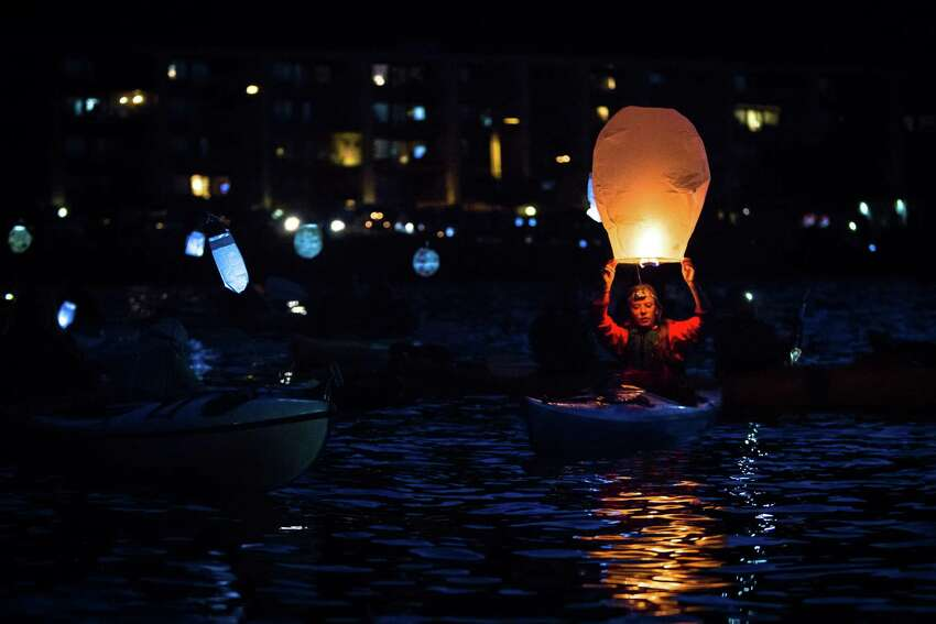 A kayaktivist prepares to release a lantern during the Shell No! Luminary Flotilla in Elliot Bay on Friday, June 5, 2015. A group of kayaktivists paddled out with lanterns and LED panels to protest Shell's Polar Pioneer anchored in Seattle and promote the preservation of the Arctic.