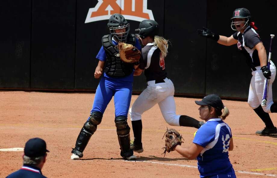 Huffman baserunner Kylie George, center, gets an elbow from Needville catcher Megan Crosby as she tries to score in the bottom of the 5th inning of their Class 4A UIL Softball State Championship final at McCombs Field in Austin on Saturday, June 6, 2015. (Photo by Jerry Baker/Freelance) Photo: Jerry Baker, For The Chronicle