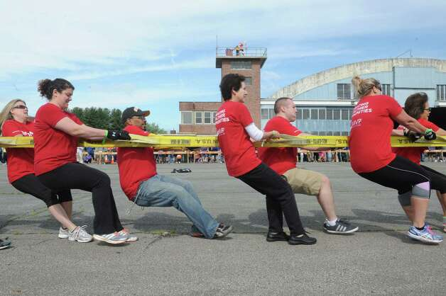 Members of the MVP Health team try their hands at pulling a C130 Hercules from the 109th Air National Guard Base during the MVP Health Care Corporate Challenge Airplane Pull at the Empire State Aerosciences Museum on Saturday June 6, 2015 in Glenville , N.Y.  (Michael P. Farrell/Times Union) Photo: Michael P. Farrell / 00032154A