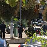 Oakland police examine the scene where an officer shot and killed a man carrying a gun in a BMW at Lake Park and Lakeshore avenues near Lake Merritt.