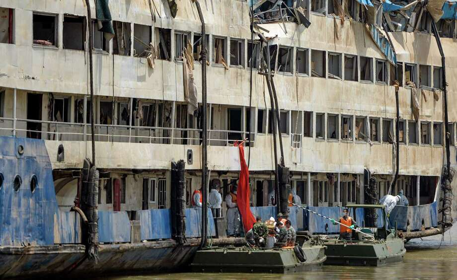 Rescuers work in the hull of the upright Eastern Star ship Saturday on the Yangtze River. Disaster teams stabilized the river cruiser in an upright position Friday and searched it for more bodies, raising the death toll to 396 and making the capsizing China's deadliest boat disaster in nearly seven decades. Photo: Bai Yu, SUB / Xinhua