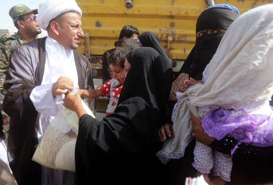 At a refugee camp south of Fallujah, a representative of Iraq's Shiite spiritual leader Grand Ayatollah Ali Sistani's office distributes bags of food to displaced Iraqis who fled Ramadi after it was seized by the IS.  Photo: AHMAD AL-RUBAYE, Staff / AFP