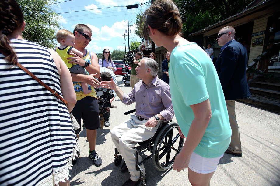 Texas Gov. Greg Abbott greets shoppers as he visits downtown Wimberley in June. At right in background is a member of his security detail. Recent figures show the security overtime costs for Abbott, Lt. Gov. Dan Patrick and Attorney General Ken Paxton have been about the same as they were for their predecessors, including Rick Perry, who traveled extensively. Photo: Tom Reel /San Antonio Express-News