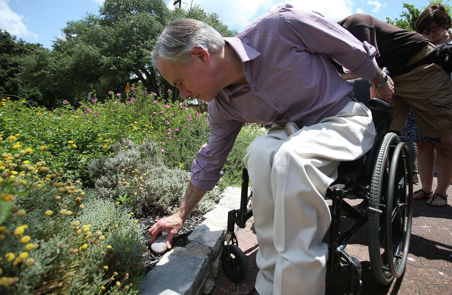 "Texas Governor Greg Abbott places a stone engraved with the word ""hope"" in a garden outside of stores in the town square as he visits business establishments in downtown Wimberley on June 6,, 2015. Photo: Tom Reel / San Antonio Express-News"