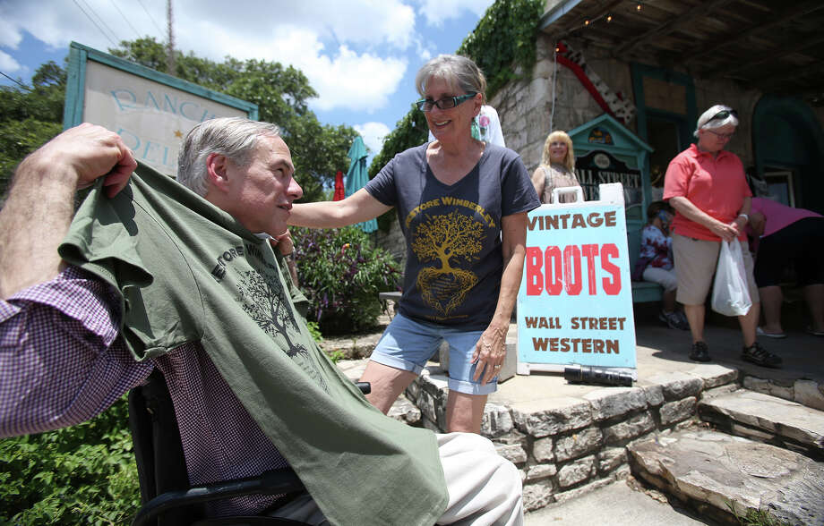 "Gov. Greg Abbott is given a ""Restore Wimberley"" shirt by its designer, Mary Owens, as he visits businesses in downtown Wimberley this month. Owens and Brandi Silva have raised over $30,000 for flood relief by selling the shirts. Photo: Tom Reel /San Antonio Express-News"