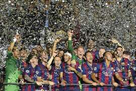 TOPSHOTS Barcelona's players celebrate after the UEFA Champions League Final football match between Juventus and FC Barcelona at the Olympic Stadium in Berlin on June 6, 2015. FC Barcelona won the match 1-3.        AFP PHOTO / LLUIS GENELLUIS GENE/AFP/Getty Images